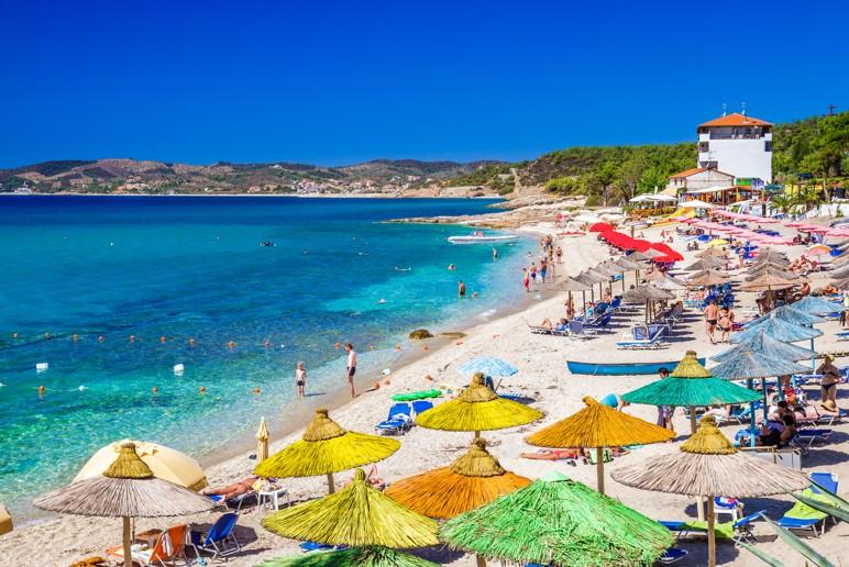 Pefkari beach near Potos, tourists enjoying a nice summer day at the beach in Thassos